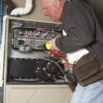 Repairman servicing or repairing basement furnace unit